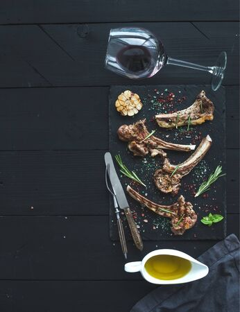 Grilled lamb chops. Rack of Lamb with garlic, rosemary and spices on slate tray, wine glass, oil in a saucer over black wood background. Top view, copy space Stock Photo