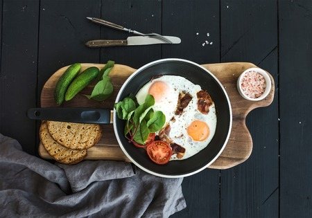 eggs and bacon: Pan of fried eggs, bacon, tomatoes with bread, mangold and cucumbers on rustic wooden serving board over dark table surface, top view
