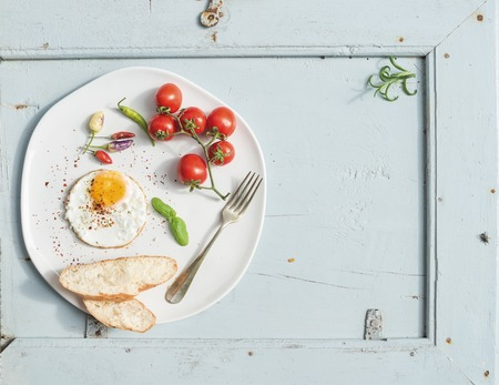 copy space: Breakfast set. Fried egg, bread slices, cherry tomatoes, hot peppers and herbs on white ceramic plate over light blue wooden backdrop, top view, copy space