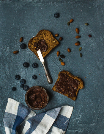 multi grain sandwich: Whole grain bread toasts with organic vegan chocolate peanut butter, blueberry, nuts over grunge grey backdrop, top view Stock Photo
