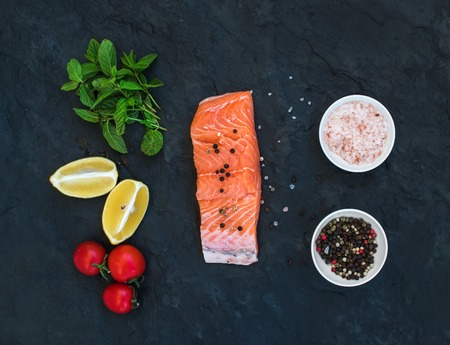 hierba buena: Ingredients. Raw salmon filet, lemon, cherry tomatoes, fresh mint and spices over dark stone backdrop, top view Foto de archivo