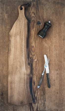pepperbox: Kitchen-ware set. Old rustic serving board, knive and fork, pepperbox on a old wooden background, top view