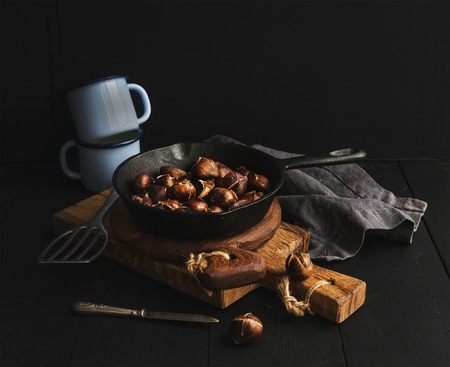 photography background: Roasted chestnuts in skillet cooking pan over rusti wooden boards, blue enamel mugs, towel on dark background, selective focus.