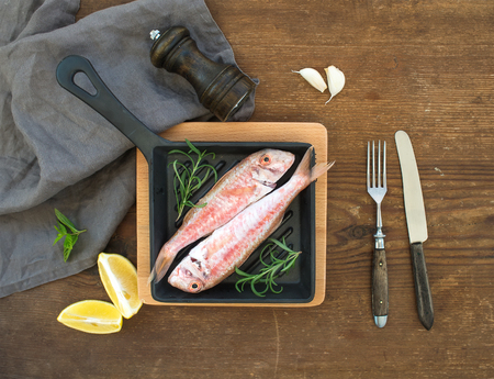 goatfish: Raw uncooked Red Mullet fish in a cooking pan with rosemary, lemon and garlic over rustic wooden background, top view