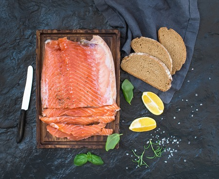 salmon filet: Smoked salmon filet with lemon, fresh herbs and bred on wooden serving board over dark stone backdrop, top view