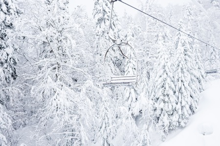 fallout: Old cable ski lift with no passengers going across the coniferous forest in Kolasin 1450 mountain ski resort near the town of Kolasin in Montenegro after a heavy snowfall on a winter day Stock Photo