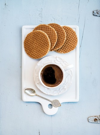 Dutch caramel stroopwafels and cup of black coffee on white ceramic serving board over light blue wooden backdrop, top view