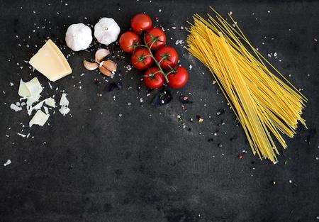 식품 프레임입니다. 파스타 재료. 지향 체리 토마토, 스파게티 파스타, 마늘, 바질, 치즈와 어두운 grunge 배경에 향신료, 복사 공간, 탑 뷰, 가로
