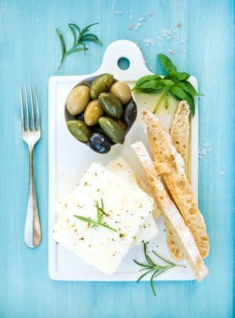 Fresh feta cheese with olives, basil, rosemary and bread slices on white ceramic serving board over bright turquoise blue painted wooden background, top view