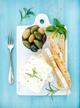 cabra: queso feta fresca con aceitunas, albahaca, romero y rebanadas de pan en la tarjeta blanca que sirve de cerámica de más de azul turquesa brillante pintado fondo de madera, vista desde arriba