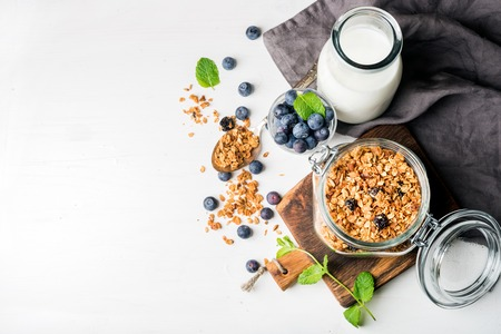 Healthy breakfast ingrediens. Homemade granola in open glass jar, milk or yogurt bottle, blueberries and mint on white wooden background, top view, copy space