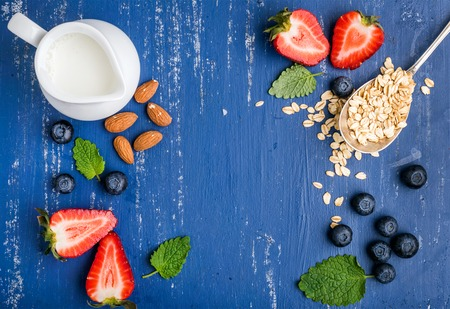 Healthy breakfast ingredients food frame. Oatmeal in spoon, milk in creamer, berries, almond and mint on painted blue wooden background, top view, copy space