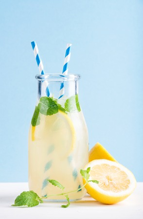 Bottle of homemade lemonade with mint, ice and lemons, paper straws and pastel blue background, selective focus