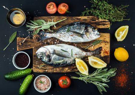 Dorado cru frais ou daurade poisson avec citron, herbes, huile, légumes et épices sur planche de bois rustique sur fond noir, vue de dessus