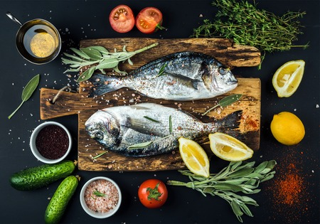 sea bream: Fresh uncooked dorado or sea bream fish with lemon, herbs, oil, vegetables and spices on rustic wooden board over black backdrop, top view