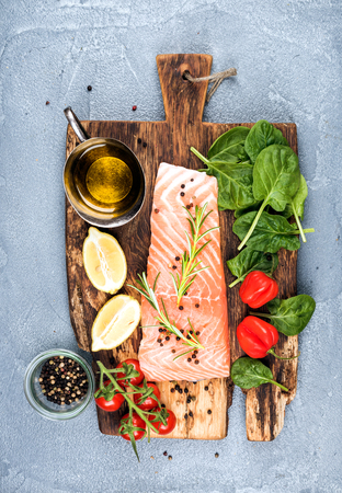 Ingredients for cooking healthy dinner. Raw salmon fillet, spinach, tomatoes, olive oil, lemon, peppers, rosemary and spices on a rustic wooden board over concrete textured grey background. Top view, vertical