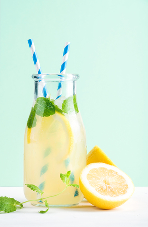 Bottle of homemade lemonade with ice and lemons, paper straws and pastel mint  background, selective focus