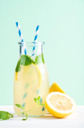 Fles zelfgemaakte limonade met ijs en citroenen, papier rietjes en pastel mint achtergrond, selectieve aandacht