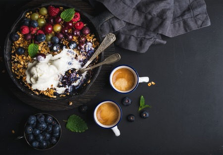 ice cram: Healthy breakfast. Oat granola crumble with fresh berries, seeds and ice-cream in iron skillet pan on dark wooden board and cups of coffee over black backdrop, top view, copy space
