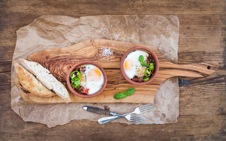 clay craft: Country style breakfast set. Eggs baked in separate clay cups with tomatoes, peppers, fresh basil, bread slices on rustic board over oily craft paper and wooden background, top view Stock Photo
