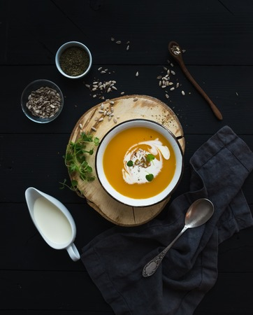 Pumpkin soup with cream, seeds and spices in rustic metal bowl over grunge black background. Top view Stock Photo