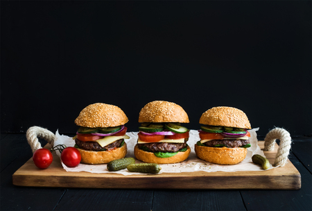 Fresh beef burgers with cheese, vegetables, pickles and spicy tomato sauce on paper over rustic wooden tray, black background, copy space Stok Fotoğraf