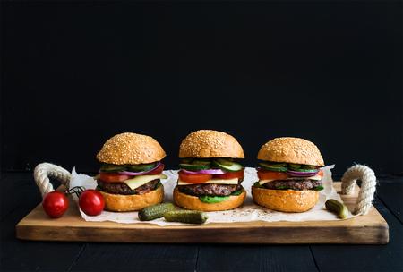 hamburguesa: hamburguesas de carne fresca con queso, verduras, encurtidos y salsa de tomate picante en papel sobre la bandeja de madera rústica, fondo negro, copia espacio