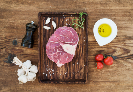 cross cut: Raw fresh beef meat cross cut for ossobuco cut with garlic cloves, cherry tomatoes, rosemary, pepper, oil and salt on serving board over rustic wooden background, top view Stock Photo