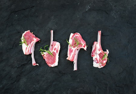 roast lamb: Raw lamb chops. Rack of Lamb with rosemary and spices over black slate stone background, top view Stock Photo
