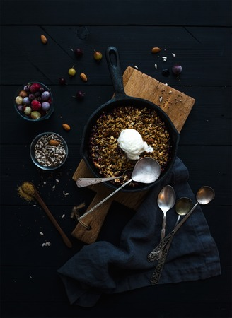 ice cram: Healthy breakfast. Oat granola crumble with frozen fresh berries,  seeds and ice-cream scoopin irom skillet pan on rustic wooden board over dark backdrop, top view