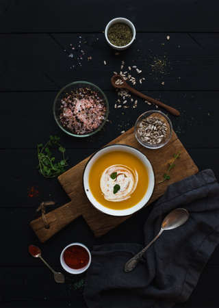 over black: Pumpkin soup with cream, seeds and spices in rustic metal bowl over grunge black background. Top view Stock Photo