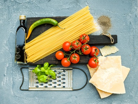 metal grater: Ingredients for cooking pasta. Spaghetti on dark wooden board, Parmesan cheese, cherry tomatoes, metal grater, olive oil and fresh basil on grey-blue concrete background, top view Stock Photo