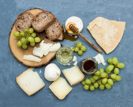 food still: Cheese appetizer selection or wine snack set. Variety of italian cheese, green grapes, bread slices and honey on round wooden board over grey-blue concrete backdrop, top view