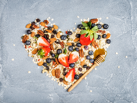 Ingrediënten voor het koken gezond ontbijt in de vorm van hart. Aardbeien, bosbessen, noten, havervlokken, gedroogde vruchten, honing met drizzlier op geweven concrete achtergrond, bovenaanzicht
