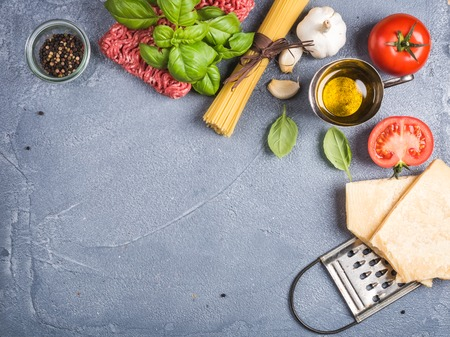 metal grater: Ingredients for cooking pasta Bolognese. Spaghetti, Parmesan cheese,  tomatoes, metal grater, olive oil, garlic, minsed meat, pepper and fresh basil on grey concrete background, top view, copy space