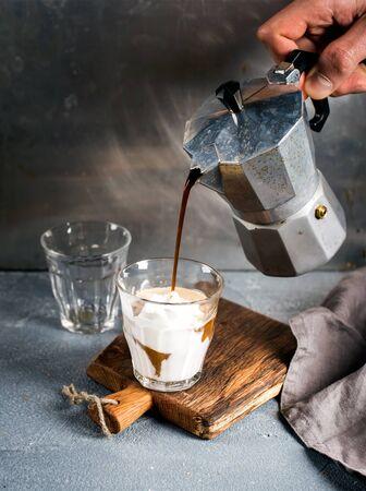 comida italiana: Un vaso de caf� con helado en una tabla de madera r�stica. Bebida se vierte de una olla de acero italiano Moka sostenida por la mano del hombre, fondo gris Foto de archivo
