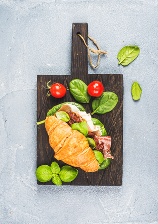 croissant: Croissant sandwich with smoked meat Prosciutto di Parma, sun dried tomatoes, fresh spinach and basil on dark wooden board over stone textured grey background, top view Stock Photo