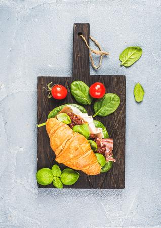 bocadillo: s�ndwich de croissant con jam�n ahumado de la carne de Parma, tomates secados al sol, espinaca fresca y albahaca sobre plancha de madera oscura sobre la piedra con textura de fondo gris, vista desde arriba