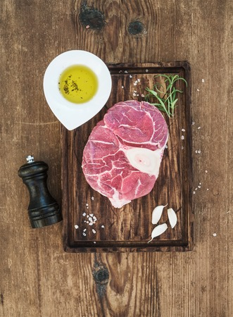 cross cut: Raw fresh beef meat cross cut for ossobuco cut with garlic cloves, rosemary, pepper, oil and salt on serving board over rustic wooden background, top view, vertical