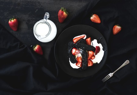 grunge silverware: Black biscotti and strawberry dessert with sweet cream over black backdrop, top view