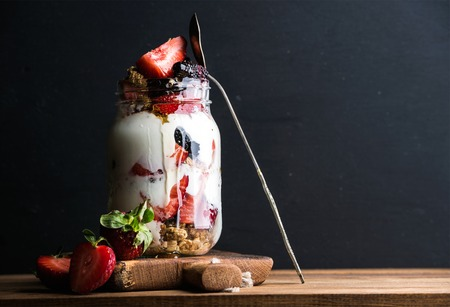 Yogurt oat granola with strawberries, mulberries, honey and mint leaves in tall glass jar on black backdrop, selective focus, copy space