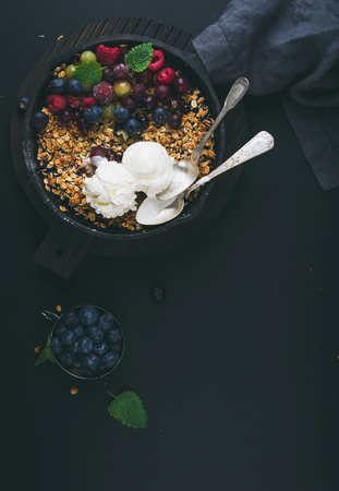 ice cram: Healthy breakfast. Oat granola crumble with fresh berries, seeds and ice-cream in iron skillet pan on dark wooden board over black backdrop, top view, vertical