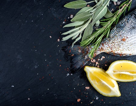 Tail of fresh raw Dorado or sea bream fish on black slate stone board with spices, herbs, lemon and salt. Top view, copy space