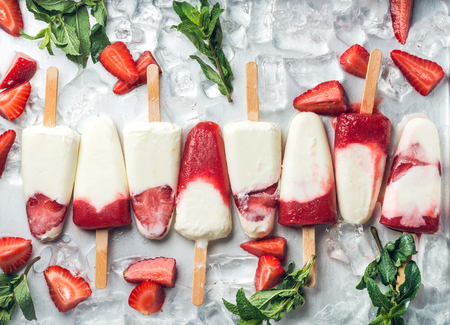 Strawberry yogurt ice pop with mint over steel tray background. Top view
