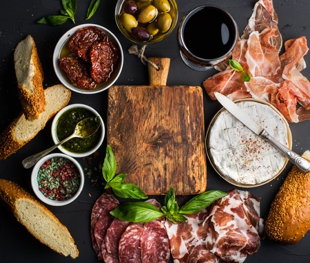 Wine snack set with empty wooden board in center. Glass of red, meat selection, mediterranean olives, sun-dried tomatoes, baguette slices, camembert cheese and spices on black background, top view, copy space