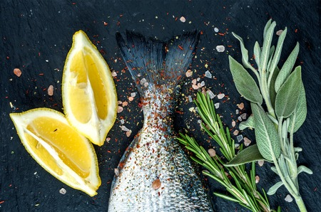 sea bream: Tail of fresh raw Dorado or sea bream fish on black slate stone board with spices, herbs, lemon and salt. Top view