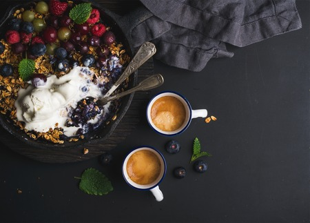 ice cram: Healthy breakfast. Oat granola crumble with fresh berries, seeds and ice-cream in iron skillet pan, coffee cups on dark wooden board over black backdrop, top view, copy space