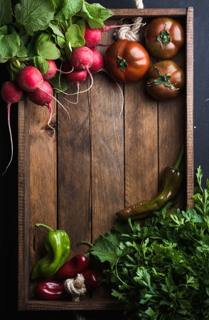Fresh raw vegetable ingredients for healthy cooking or salad making in rustic wooden tray over black background, top view, copy space. Diet or vegetarian food concept. Vertical