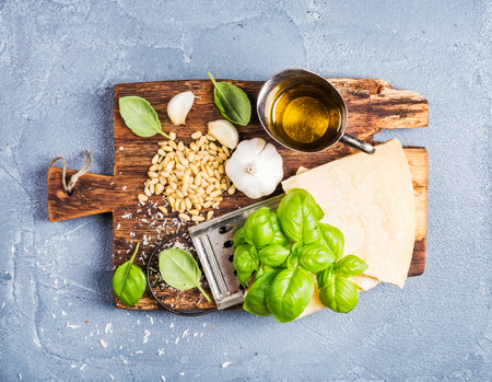 metal grater: Ingredients for cooking Pesto sauce. Parmesan cheese, metal grater, fresh basil, olive oil, garlic and pine nuts on old rustic wooden board over grey concrete background, top view Stock Photo