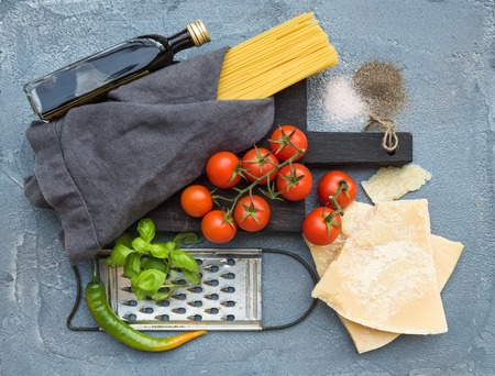 metal grater: Ingredients for cooking pasta. Spaghetti on dark wooden board, Parmesan cheese, cherry tomatoes, metal grater, olive oil and fresh basil on grey concrete background, top view